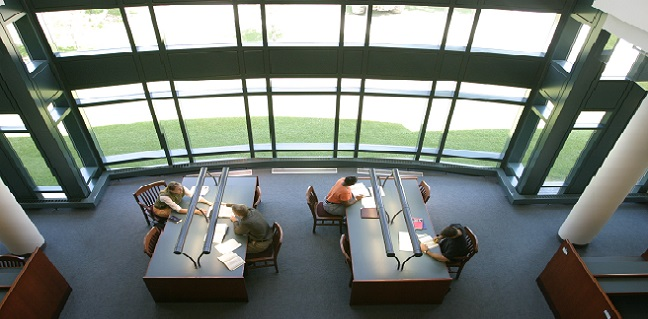 Students study near large windows in the law library