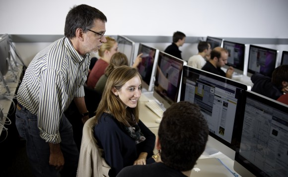 Two students working together in a computer lab as a faculty member looks on.