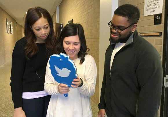 Three students standing in a hallway in Meredith Hall; the student in the center is holding a Twitter mirror.