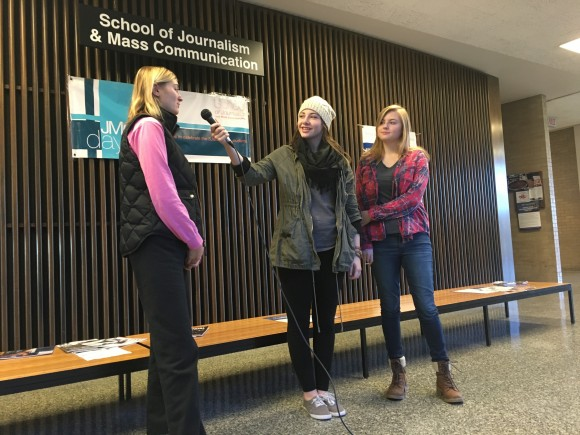 Two Journalism students interview a woman in the lobby of Meredith Hall.