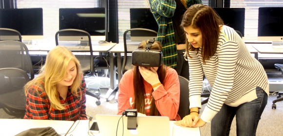 Three first-year SJMC students in the Multimedia Lab; the student in the center is wearing a virtual reality headset.