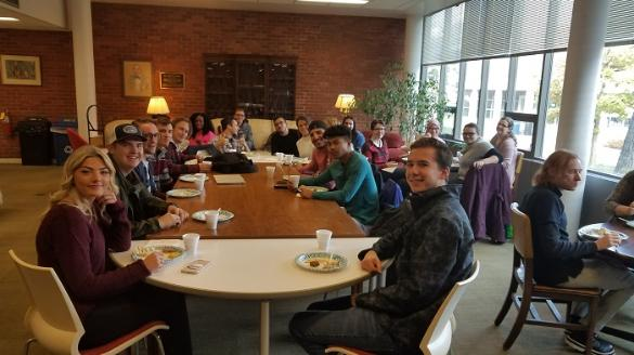 Students eating around a conference table