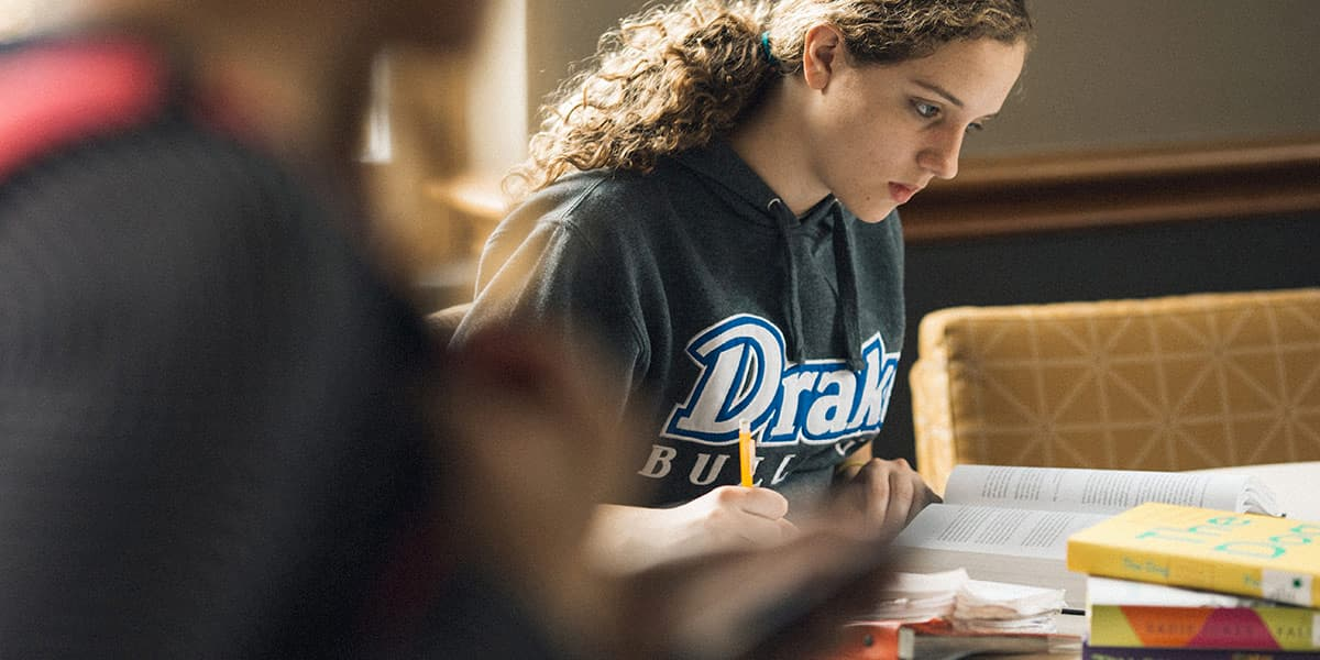 Drake University student studying in the library