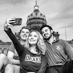 Three Drake University students in front of the Des Moines capital taking a selfie